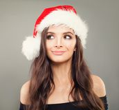 圣诞老人帽子的美丽的年轻圣诞节模型妇女 库存图片