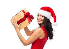 圣诞老人帽子的美丽的性感的妇女有礼物盒的 免版税库存照片