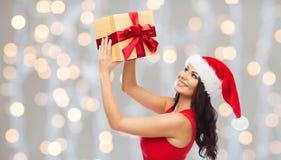 圣诞老人帽子的美丽的性感的妇女有礼物盒的 免版税库存图片