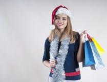 圣诞老人帽子的美丽的愉快的妇女拿着许多购物袋 库存照片