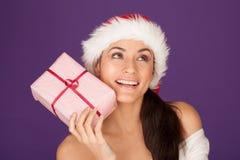 圣诞老人帽子的美丽的浅黑肤色的男人与礼品 免版税库存图片