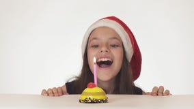 圣诞老人帽子的美丽的淘气女孩少年吹灭在一个欢乐蛋糕的一个蜡烛在白色背景 图库摄影