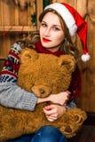 圣诞老人帽子的美丽的白肤金发的女孩坐椅子 库存照片