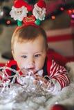圣诞老人帽子的美丽的矮小的男婴庆祝圣诞节和戏剧与诗歌选 新年` s假日 有礼物的小孩在 免版税图库摄影