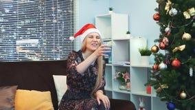 圣诞老人帽子的美女等待和情感地庆祝新年的来临 股票录像