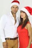 戴圣诞老人帽子的美好的年轻夫妇 免版税图库摄影