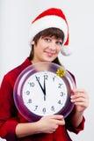 圣诞老人帽子的蓝眼睛的美丽的女孩有时钟的 库存照片