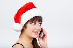 圣诞老人帽子的蓝眼睛的美丽的女孩有电话的 库存图片