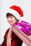 圣诞老人帽子的蓝眼睛的美丽的女孩有礼物的 库存图片