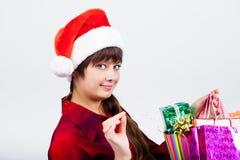 圣诞老人帽子的蓝眼睛的美丽的女孩有礼物的 库存照片