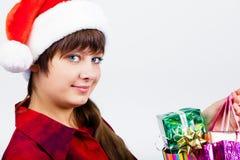 圣诞老人帽子的蓝眼睛的美丽的女孩有礼物的 免版税库存照片
