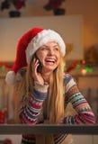 圣诞老人帽子的谈微笑的十几岁的女孩手机在厨房里 库存图片