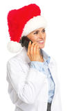 圣诞老人帽子的谈愉快的医生的妇女手机 库存图片