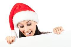 圣诞老人帽子的逗人喜爱的女孩。 查出 库存照片