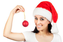 圣诞老人帽子的逗人喜爱的女孩与圣诞节球 免版税库存图片
