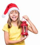 戴圣诞老人帽子的逗人喜爱的女孩 库存照片