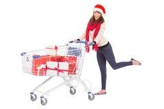 圣诞老人帽子的逗人喜爱的妇女有购物台车的 免版税库存图片