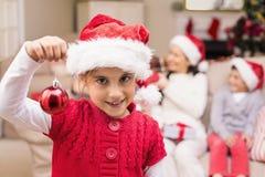 戴圣诞老人帽子的逗人喜爱的小女孩拿着中看不中用的物品 库存图片