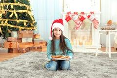 圣诞老人帽子的逗人喜爱的小女孩有可口曲奇饼板材的在家 库存照片