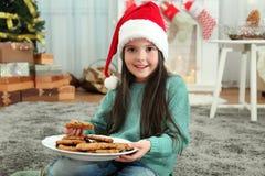 圣诞老人帽子的逗人喜爱的小女孩有可口曲奇饼板材的  免版税库存照片