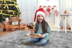 圣诞老人帽子的逗人喜爱的小女孩有可口曲奇饼板材的  免版税图库摄影