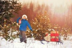 圣诞老人帽子的逗人喜爱的小男孩在多雪的森林里运载有礼物的一个木雪撬 库存图片