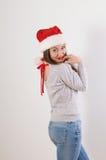 圣诞老人帽子的逗人喜爱的少妇在白色背景 图库摄影