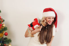圣诞老人帽子的逗人喜爱的滑稽的妇女有在圣诞节tr附近的玩具狗的 免版税库存图片