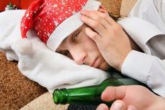 圣诞老人帽子的酒醉少年 库存图片