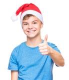 戴圣诞老人帽子的青少年的男孩 免版税库存照片