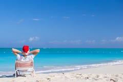圣诞老人帽子的年轻人在海滩假期时 库存图片
