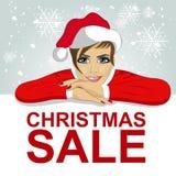 圣诞老人帽子的年轻可爱的妇女在有红色圣诞节销售文本的空白的委员会倾斜了 免版税库存图片
