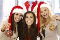 圣诞老人帽子的年轻女性办公室工作者 免版税库存照片