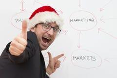 戴圣诞老人帽子的满意的商人 免版税库存图片