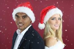 戴圣诞老人帽子的年轻混杂的夫妇 图库摄影