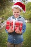 戴圣诞老人帽子的年轻男孩拿着圣诞节礼物外面 免版税库存图片