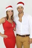 戴圣诞老人帽子的年轻白种人夫妇 图库摄影