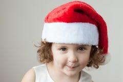 圣诞老人帽子的滑稽的矮小的卷曲白肤金发的女孩 免版税库存照片