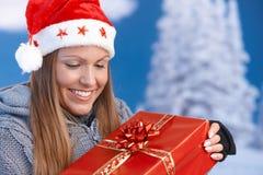 圣诞老人帽子藏品圣诞节礼物的妇女 免版税库存照片