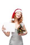 圣诞老人帽子藏品符号的新偶然女孩 免版税库存图片