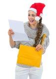 圣诞老人帽子读取圣诞节信函的愉快的妇女 库存照片
