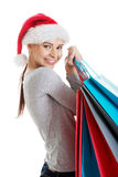 圣诞老人帽子运载的购物袋的美丽的妇女。 免版税库存图片