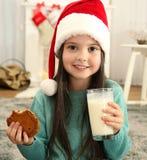 圣诞老人帽子饮用奶和吃的逗人喜爱的小女孩 免版税图库摄影
