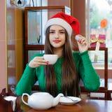 圣诞老人帽子饮用的茶的年轻美丽的妇女在咖啡馆 免版税库存照片