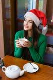 圣诞老人帽子饮用的茶的年轻美丽的妇女在咖啡馆 库存图片