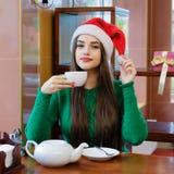 圣诞老人帽子饮用的茶的年轻美丽的妇女在咖啡馆 库存照片