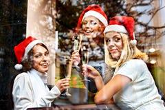 圣诞老人帽子饮用的香槟的妇女。 免版税库存图片