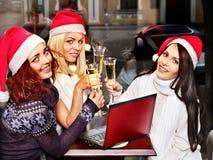 圣诞老人帽子饮用的香槟的妇女。 免版税库存照片
