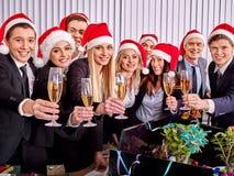圣诞老人帽子饮用的香槟的集团人在Xmas 免版税图库摄影