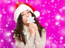 圣诞老人帽子画象的女孩与摆在桃红色颜色背景,圣诞节假日概念,愉快的大雪花玩具和情感 库存图片